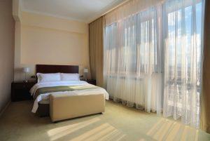 Rideaux de voiles pour une chambre a coucher avec literie confortable.