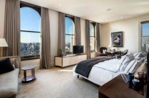 Une belle et somptueuse chambre a coucher avec des rideaux beige et une literie sur mesure. Remarqué également la jette sur le lit qui apporte une touche de douceur.