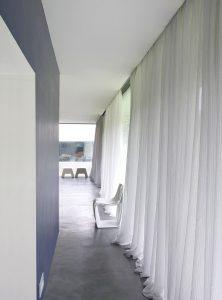 Rideaux voilages en lin blanc pour couvrir un mur de fenêtre.